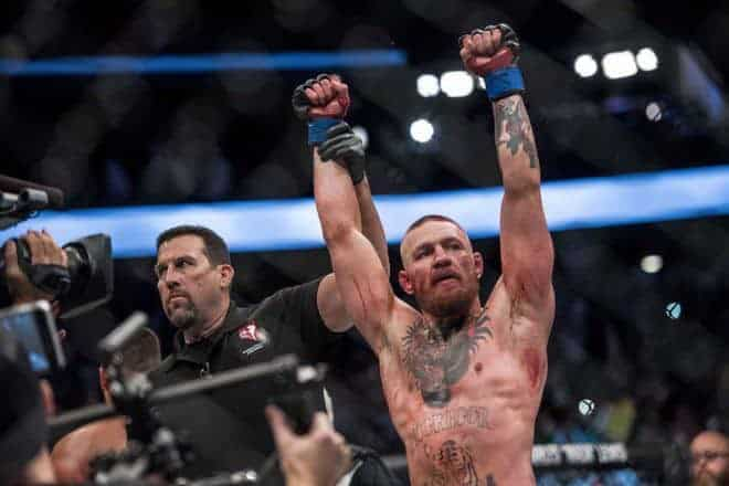 Aug 20, 2016; Las Vegas, NV, USA; Conor McGregor (blue gloves) reacts to fight with Nate Diaz (red gloves) during UFC 202 at T-Mobile Arena. Mandatory Credit: Joshua Dahl-USA TODAY Sports